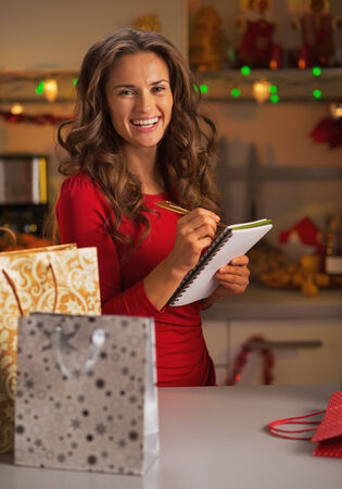 christmas shopping: Happy young woman with shopping bags checking list of gifts in christmas decorated kitchen