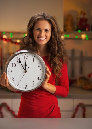 Portrait of smiling young woman holding clock in christmas decorated kitchen photo