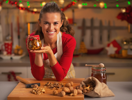 woman cooking: Happy young housewife showing jar with honey nuts