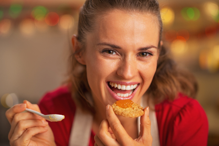 Portrait of smiling young housewife eating orange jam photo