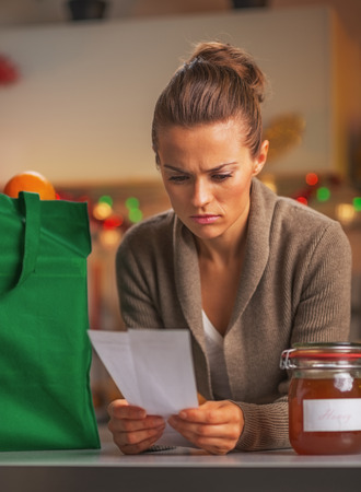 disquieted: Concerned young housewife looking on checks after christmas shopping