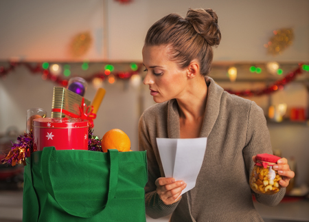 disquieted: Concerned young housewife with checks exploring christmas purchases Stock Photo
