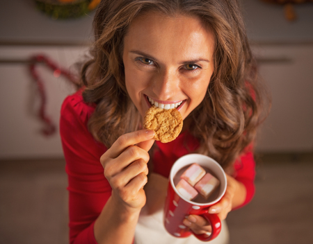 Smiling young housewife eating christmas cookies in kitchen photo