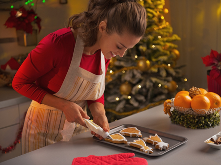 cook house: Happy young housewife decorating christmas cookies with glaze
