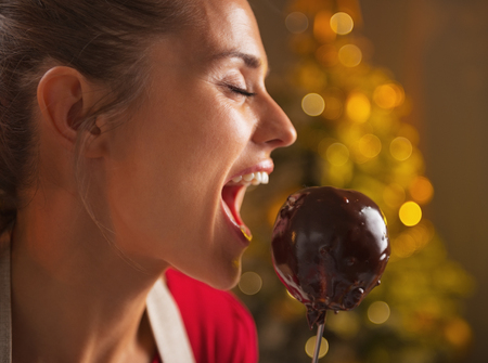 Happy young housewife eating apple in chocolate glaze in christmas decorated kitchen photo