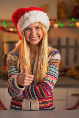 Smiling teenage girl in santa hat showing thumbs up in christmas decorated kitchen photo