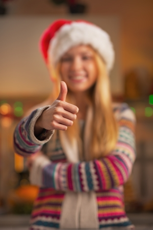 Closeup on smiling teenage girl in santa hat showing thumbs up in christmas decorated kitchen photo
