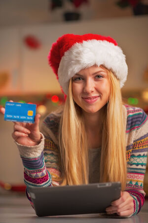 Smiling teenage girl in santa hat with tablet pc showing credit card in christmas decorated kitchen photo
