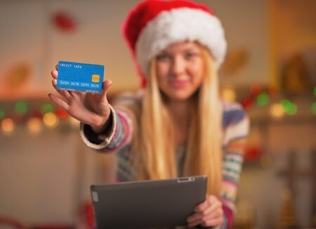 Closeup on smiling teenage girl in santa hat with tablet pc showing credit card in christmas decorated kitchen photo