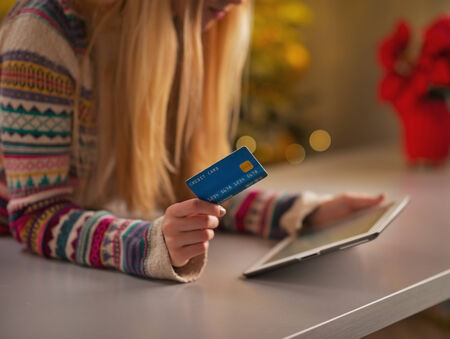 Closeup on teenage girl with credit card using tablet pc in christmas decorated kitchen Stock Photo - 24283507
