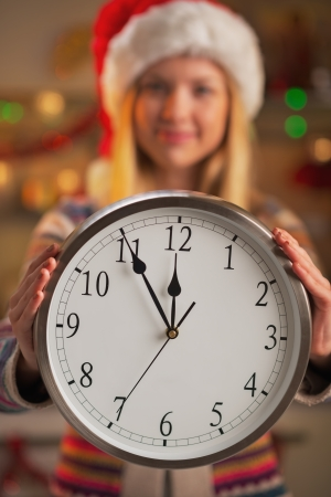 Closeup on smiling teenage girl in santa hat showing clock photo