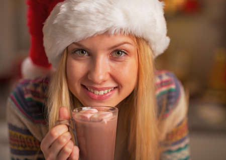 Portrait of happy teenage girl in santa hat with cup of hot chocolate photo