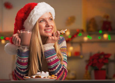 Thoughtful teenage girl in santa hat with cup of hot chocolate and christmas cookie in christmas decorated kitchen photo