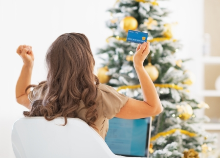 Young woman with credit card and laptop rejoicing success near christmas tree Stock Photo - 24283732