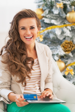 Happy young woman making online shopping with tablet pc near christmas tree photo