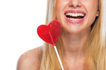 Closeup on smiling teenage girl with heart shaped lollypop Stock Photo - 24293505