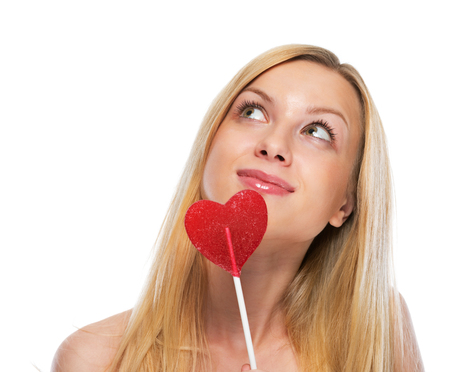Portrait of happy teenage girl with heart shaped lollypop looking on copy space photo