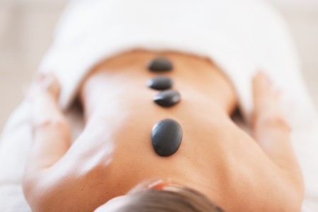 Closeup on relaxed young woman receiving hot stone massage Stock Photo - 24488906