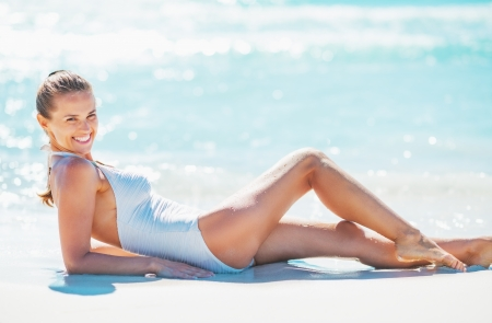 Smiling young woman laying on beach photo