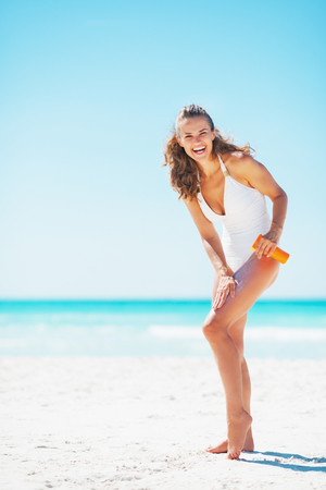 Full length portrait of smiling young woman applying sun screen creme photo