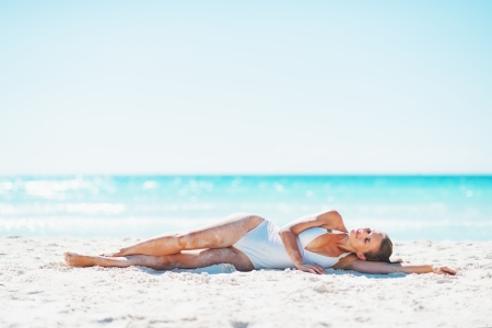 Young woman laying on beach photo