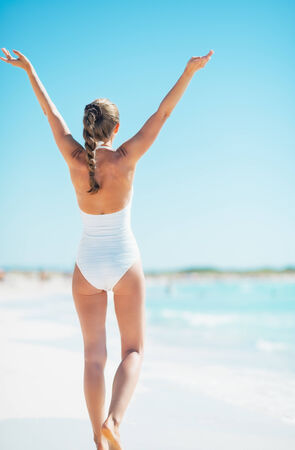 rejoicing: Young woman rejoicing on beach. rear view