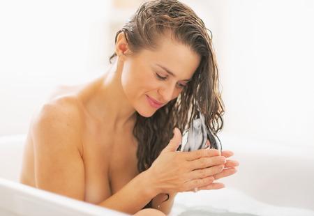 hair conditioner: Happy young woman applying hair conditioner in bathtub