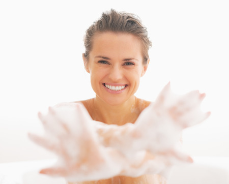 hygienics: Smiling young woman showing hands in foam Stock Photo