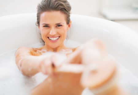 Smiling young woman washing with body brush in bathtub Stock Photo