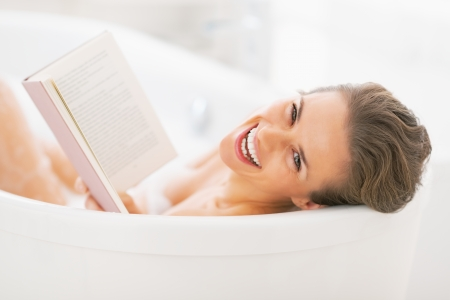 Portrait of smiling young woman reading book in bathtub. rear view