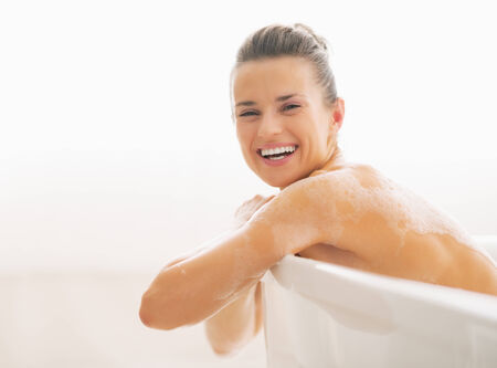 Portrait of smiling young woman sitting in bathtub photo
