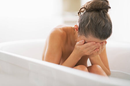 Stressed young woman sitting in bathtub photo