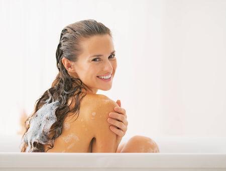 washing hair: Smiling young woman washing hair in bathtub Stock Photo