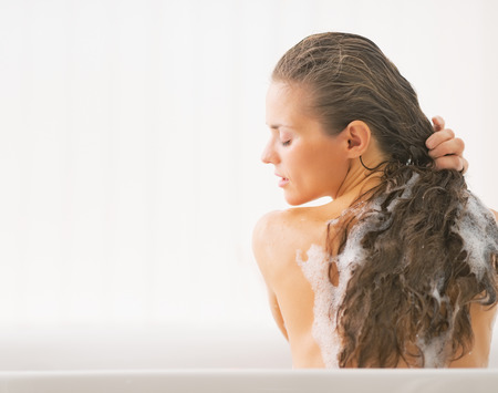 woman washing hair: Young woman washing hair in bathtub