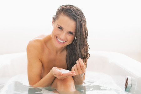 masks: Happy young woman applying hair mask in bathtub Stock Photo