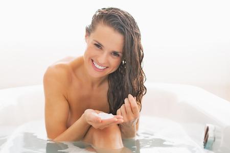 baño: Mujer joven feliz que aplica la máscara de pelo en la bañera