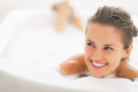 Portrait of smiling young woman laying in bathtub and looking on copy space