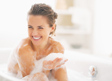 woman relaxing: Portrait of happy young woman playing with foam in bathtub