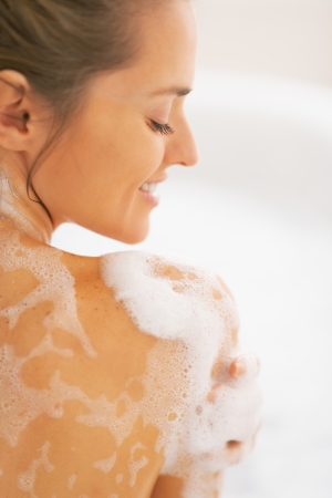 hygienics: Happy young woman washing in bathtub