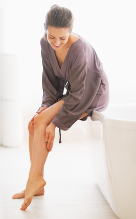softness: Young woman checking leg skin softness in bathroom