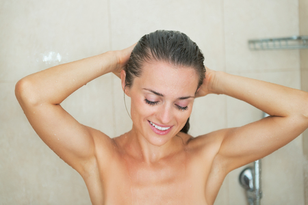 Happy young woman washing in shower Stock Photo