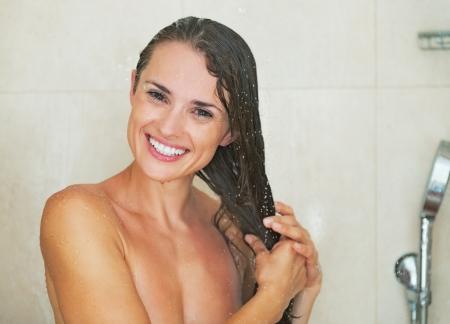 cabine de douche: Portrait de jeune femme souriante dans la douche