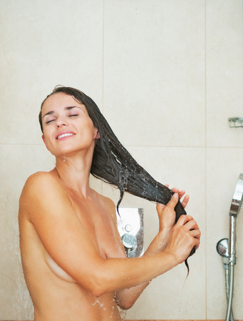 female in douche: Happy young woman washing hair in shower Stock Photo