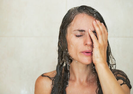 woman in shower: Portrait of stressed young woman in shower