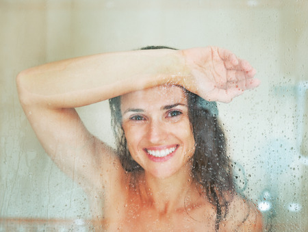 Happy young woman behind shower door photo