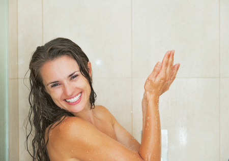 Smiling young woman washing in shower photo