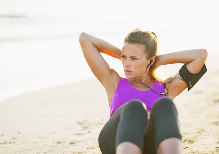 crunch: Fitness young woman doing abdominal crunch on beach Stock Photo