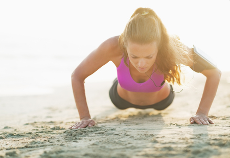 Fitness young woman doing push ups on beach photo