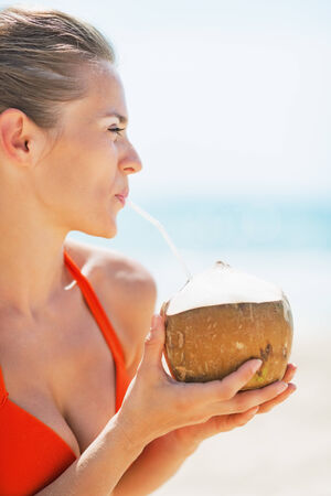 Portrait of happy young woman drinking coconut milk on beach photo