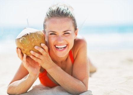 Portrait of smiling young woman on beach holding coconut photo